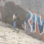 Graffiti being removed using wet abrasive blasting